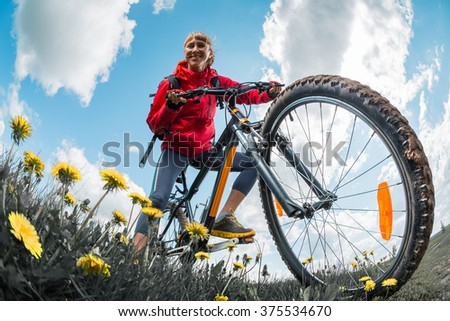 Young lady with bicycle on a spring meadow with flowers - stock photo