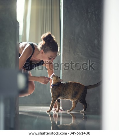 Young lady with cat on the floor at the kitchen at home - stock photo