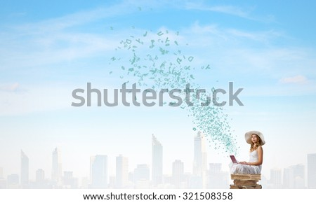 Young lady with laptop on knees sitting on pile of books - stock photo