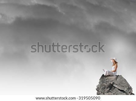 Young lady with laptop on knees sitting on top of mountain - stock photo