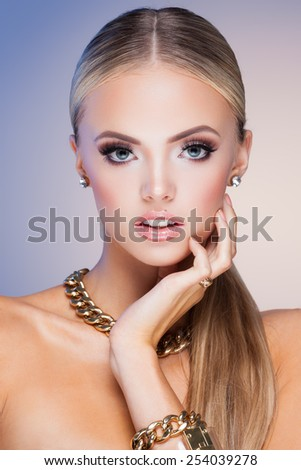 Young lady with luxury accessories on blue background - stock photo