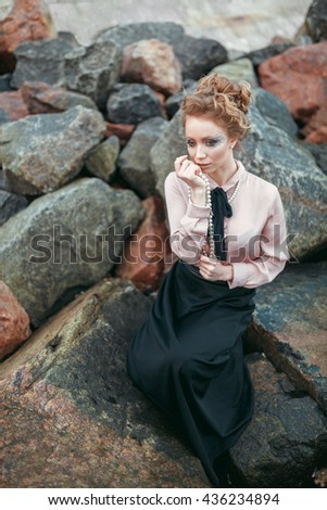 Young lady with pearl necklace is sitting on a stone near the sea. She is wearing elegant blouse and long black skirt and having stylish makeup