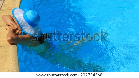 Young lady with white blue hat by the poolside - stock photo