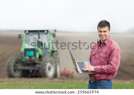 Young landowner with laptop supervising work on farmland, tractor in background - stock photo