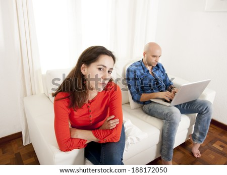 young Latin attractive couple sitting on couch with girlfriend frustrated and angry because boyfriend always  busy working or playing with tablet and computer at living room - stock photo