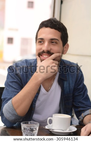 Young latin handsome man drinking coffee at an outdoor cafe. - stock photo