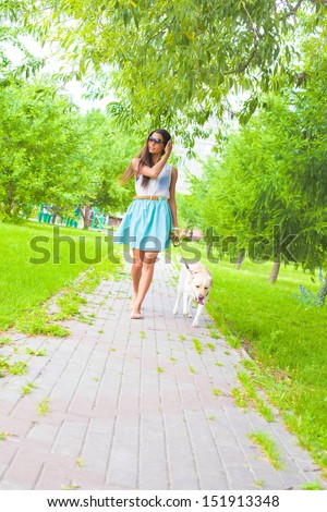 Young latin hispanic brunette Woman wear blue dress walking with white dog - labrador along the path laid paving stones Copy space for inscription