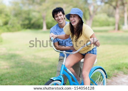 Young latin man in shorts and blue shirt helps young woman riding blue bike with green trees and grass. Horizontal shallow focused composition. - stock photo
