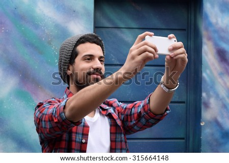 Young latin man taking a selfie. Technology concept. - stock photo