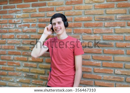 Young latin man with black headphones. Trendy and urban style. - stock photo