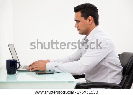 Young Latin man working at his desk with a white background