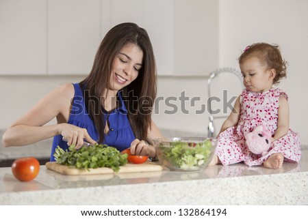 Young latin mother and her baby girl making a salad in the kitchen - stock photo