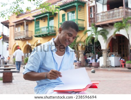 Young latin student in a colonial town reading documents - stock photo
