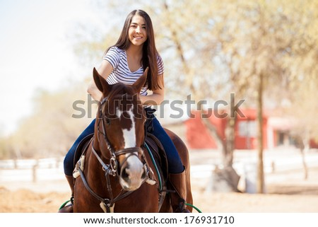 Young Latin woman enjoying a horse ride on a sunny day - stock photo