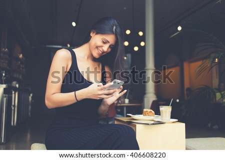 Young latin woman making self portrait on her smart phone digital camera while sitting in sidewalk cafe during lunch break. Pretty female posing while photographing herself for social network picture - stock photo