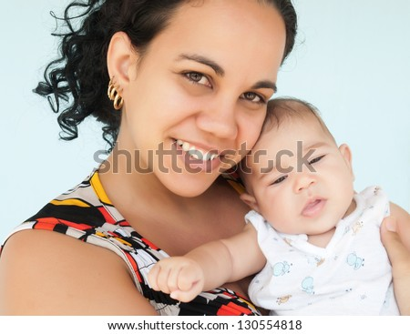 Young latin woman smiling and carrying her small baby girl - stock photo