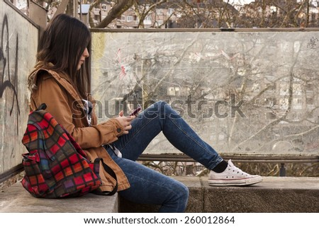 young latina girl in the street with mobile phone - stock photo