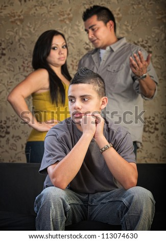 Young Latino boy in blank stare with concerned parents behind him - stock photo