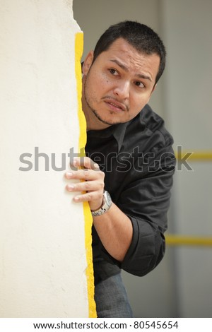 Young Latino man hiding behind a wall