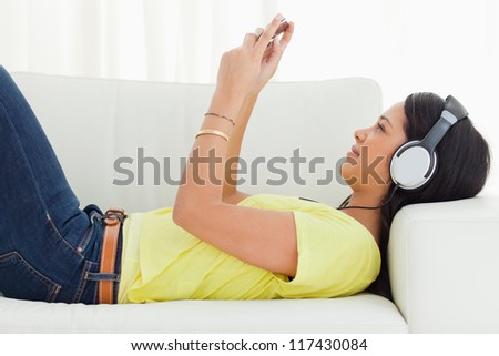Young Latino woman watching a video with her smartphone while lying on a sofa