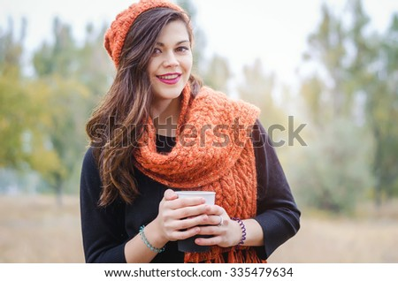 Young laughing girl with a cup of coffee (tea) for a walk in the park outdoors. Autumn weather. - stock photo