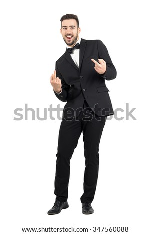 Young laughing provocative man in suit showing middle finger gesture looking at camera.  Full body length portrait isolated over white studio background.