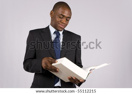 Young lawyer or business man reading a big book - stock photo