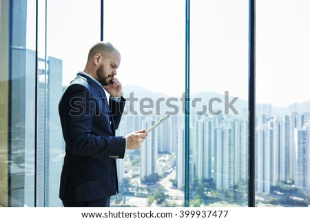 Young lawyer with serious face and digital tablet in hand is talking on mobile phone with client, while is standing in office interior near window with copy space background for your advertising text