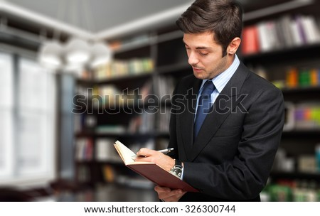 Young lawyer writing something in his studio - stock photo