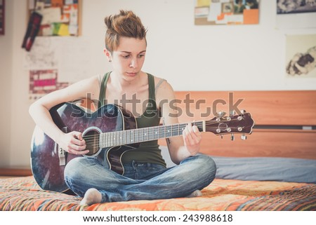 young lesbian stylish hair style woman playing guitar at home