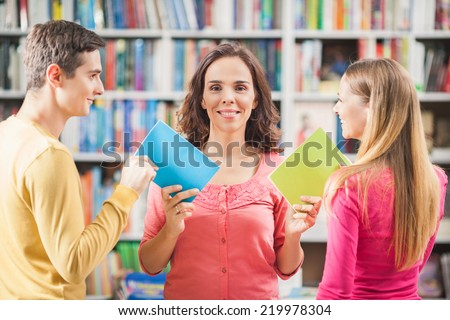 Young librarian or teacher giving books to her students - stock photo