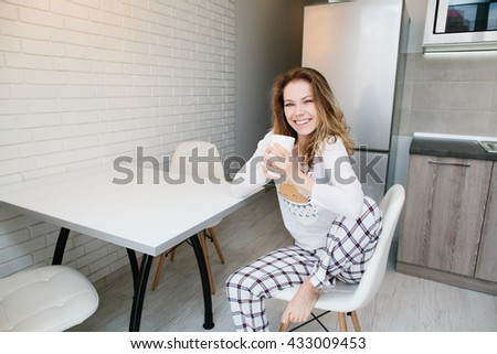 Young light brown woman in pajamas sitting on chair with white cup and smiling in white kitchen at morning