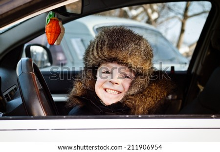 Young little boy driving a luxury car - stock photo