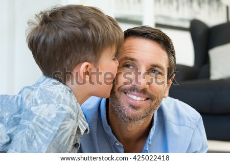 Young little boy giving a kiss on father cheek. Cute child kissing her dad at home. Loving son playing with his father. - stock photo