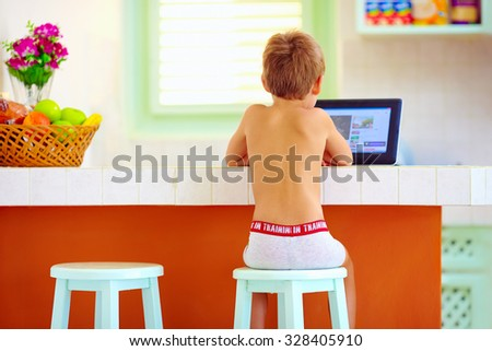 young little boy watching video through the internet, while sitting in kitchen in the morning - stock photo