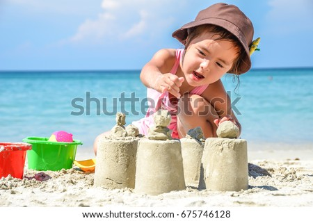 Young little Girl at the Beach Making sand castle .Fun in summer day with blue sky.Great activity for kids and family.
