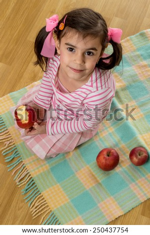 young little girl eating red apple on floor - stock photo