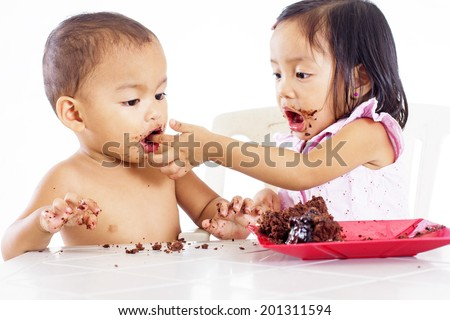 Young little girl feeding a little boy with a cake with her finger.