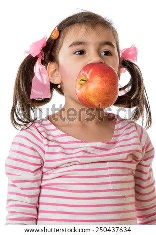 young little girl holding a big apple in her mouth - stock photo