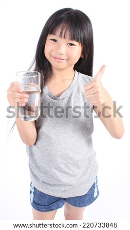 Young little girl holding a glass of water.  - stock photo