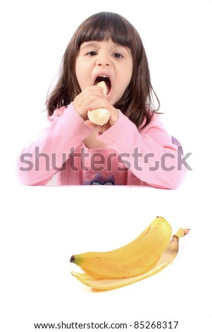 Young little girl making a funny face eating a healthy banana - stock photo