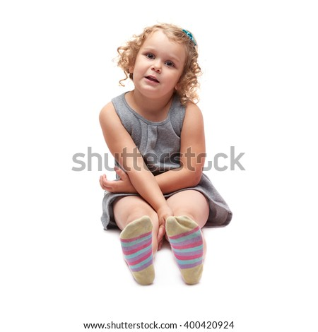 Young little girl sitting over isolated white background - stock photo