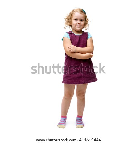 Young little girl with curly hair and crossed arms in purple dress standing over isolated white background - stock photo