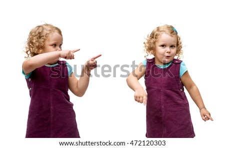 Young little girl with curly hair in purple dress standing and ponting to side copy space over isolated white background