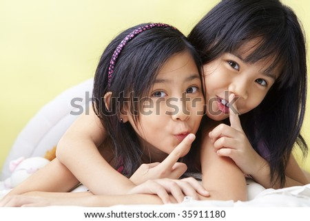young little girls shh to camera not to telling their secret - stock photo