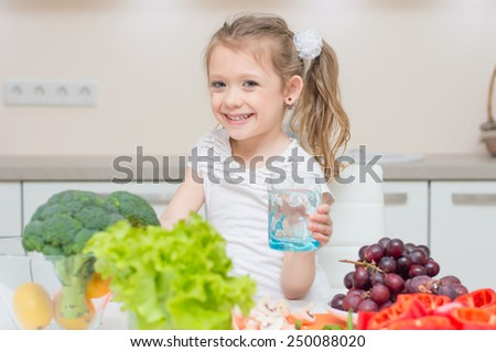 Young little pretty smiling girl gives you the glass with clean fresh water - stock photo