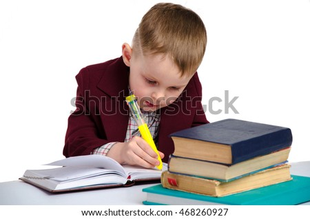 young little schoolboy in uniform writes in his notebook isolated on white background