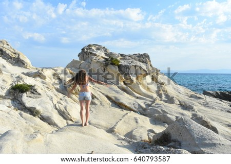 Young long hair girl walking on the rocky beach, with beautiful blue color of the sea and sky
