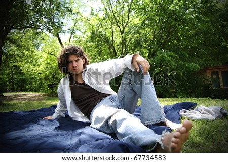 Young Long Hair man relaxing in the park - stock photo