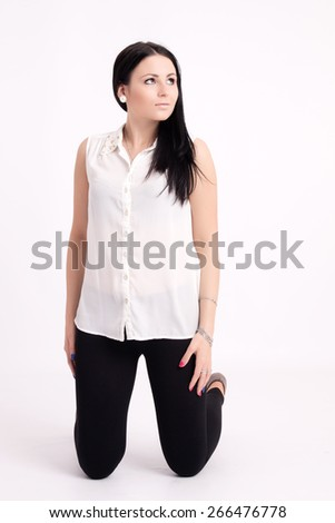 Young long-haired black-haired woman kneeling thoughtful - stock photo